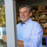 66841728 – wine shop owner holding open sign